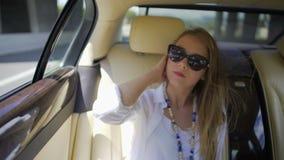 Mujer bastante rubia que disfruta de viaje en el asiento trasero del auto costoso, turismo metrajes