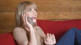 Mujer bastante rubia que habla en el teléfono en casa Imágenes de archivo libres de regalías