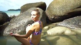Mujer bastante rubia que hace yoga entre las rocas cerca del mar durante día de verano hermoso almacen de metraje de vídeo