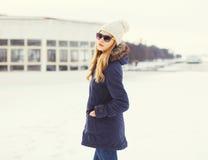 Mujer bastante rubia que lleva una chaqueta, un sombrero y gafas de sol en invierno Imagenes de archivo
