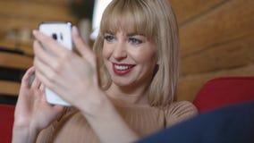 Mujer bastante rubia que manda un SMS en el teléfono en casa Imagen de archivo