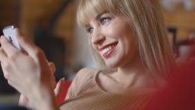 Mujer bastante rubia que manda un SMS en el teléfono en casa Imágenes de archivo libres de regalías