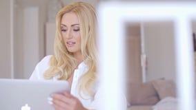 Mujer bastante rubia que mira su ordenador portátil seriamente metrajes