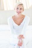 Mujer bastante rubia que sonríe en la cámara mientras que se sienta en la cama Foto de archivo