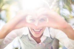 Mujer bastante rubia que sonríe en la cámara y que hace forma del corazón con sus manos fotos de archivo libres de regalías