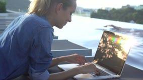 Mujer bastante rubia que trabaja en un ordenador portátil mientras que miente encendido sunbed con la natación del hombre en fond almacen de metraje de vídeo