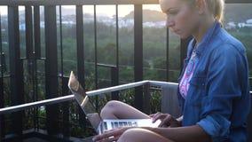 Mujer bastante rubia que trabaja en un ordenador portátil mientras que sienta y disfruta de madrugada con los pájaros que gojean  almacen de metraje de vídeo