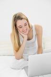 Mujer bastante tranquila que usa su cuaderno que se sienta en su cama Imagenes de archivo