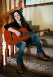 Mujer bastante triste que toca una guitarra Fotos de archivo libres de regalías