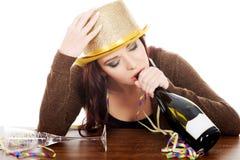 Mujer bebida joven por una tabla y con la botella vacía. Fotos de archivo libres de regalías