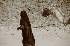 Mujer beduina con el camello Imagen de archivo