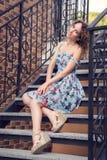 Mujer bien arreglada hermosa en un vestido azul que presenta en las escaleras con las verjas torcidas imagen de archivo libre de regalías