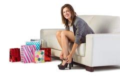 Mujer bien vestida que se sienta en el sofá que saca sus zapatos Fotografía de archivo libre de regalías
