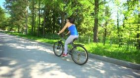 Mujer Biking que completa un ciclo en la bici Bicicleta deportiva del montar a caballo de la mujer en día de verano Vida femenina metrajes