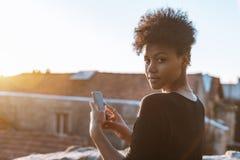 Mujer Biracial con el teléfono celular en el tejado Imagen de archivo libre de regalías