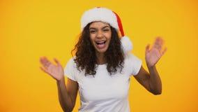 Mujer biracial feliz en saltar del sombrero de Papá Noel, sonriendo en la cámara, saludo almacen de video