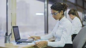 Mujer biracial hermosa que compara las cartas financieras, hembra de trabajo dura, oficina metrajes