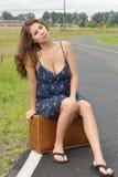 Mujer biracial hermosa que se sienta en la maleta por el camino Fotos de archivo