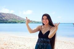 Mujer biracial joven en la playa hawaiana que hace la muestra de Hang Loose Imagenes de archivo