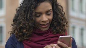 Mujer biracial joven que mira el vídeo divertido en el smartphone, tecnologías modernas almacen de video