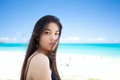 Mujer biracial joven que mira sobre hombro en la playa hawaiana Fotos de archivo