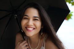 Mujer biracial sonriente hermosa o paraguas que se sostiene adolescente en rai Imagenes de archivo
