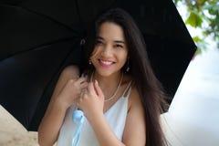 Mujer biracial sonriente hermosa o paraguas que se sostiene adolescente en rai Fotos de archivo