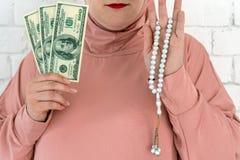 Mujer blanca con los ojos azules en un hijab rosado que lleva a cabo un rosario y d?lares en un fondo blanco imágenes de archivo libres de regalías