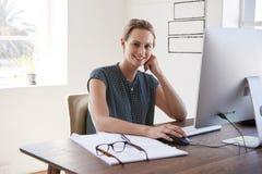 Mujer blanca sonriente que trabaja en una oficina que mira a la cámara Foto de archivo libre de regalías