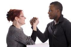 Mujer blanca y hombre negro que hacen la lucha de brazo Fotografía de archivo