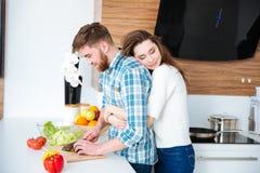 Mujer blanda que abraza a su marido mientras que él verduras del corte fotos de archivo