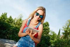 Mujer blondy joven que se sienta en un parque en un banco de piedra fotografía de archivo libre de regalías