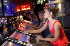 Mujer bonita alegre que juega las máquinas tragaperras en casino imagen de archivo