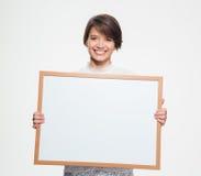 Mujer bonita alegre que lleva a cabo al tablero en blanco delante de sí misma Fotos de archivo libres de regalías