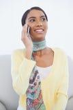 Mujer bonita alegre que se sienta en el sofá que tiene una llamada de teléfono Imagen de archivo