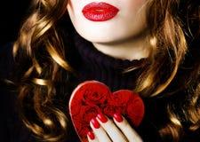 Mujer bonita atractiva hermosa joven que lleva a cabo un amor rojo de la tarjeta del día de San Valentín del maquillaje del coraz imagen de archivo libre de regalías