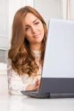Mujer bonita casual joven que usa el ordenador portátil Imagen de archivo