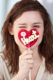 Mujer bonita con el corazón del caramelo Imagenes de archivo