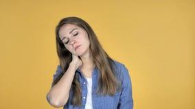 Mujer bonita con el dolor de cuello, fondo amarillo almacen de metraje de vídeo