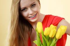 Mujer bonita con el manojo amarillo de los tulipanes Imagen de archivo