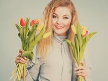 Mujer bonita con el manojo amarillo rojo de los tulipanes Foto de archivo