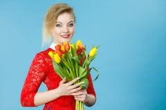 Mujer bonita con el manojo amarillo rojo de los tulipanes Foto de archivo libre de regalías