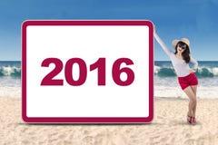 Mujer bonita con el número 2016 en la playa Fotos de archivo libres de regalías