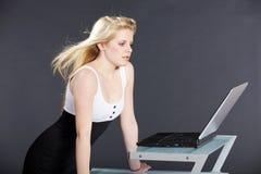 Mujer bonita con el ordenador portátil y el pelo del vuelo Fotos de archivo