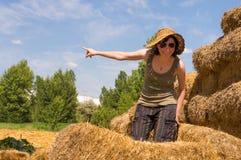 Mujer bonita con el sombrero que se coloca en balas de la paja y que señala su finger hacia el cielo azul imagen de archivo