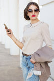Mujer bonita con el teléfono a disposición Imagen de archivo libre de regalías