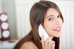 Mujer bonita con el teléfono que se sienta en cama Fotos de archivo libres de regalías