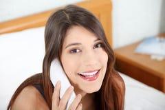 Mujer bonita con el teléfono que se sienta en cama Fotografía de archivo