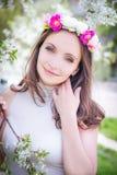 Mujer bonita con la guirnalda entre el flor de la manzana Foto de archivo