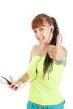 Mujer bonita con la música que escucha y el pulgar u de los auriculares el mostrar Fotos de archivo libres de regalías